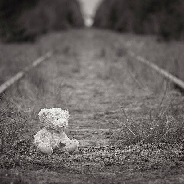 lonely-teddy-bear-sitting-on-the-rail-tracks-lost-childhood-robert-pastryk